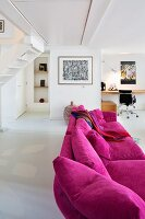 Magenta couch in modern, open-plan interior with desk and classic chair in background