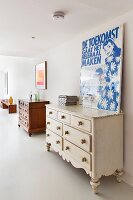 Two rustic, wooden chests of drawers, one plain, one white, below posters on wall