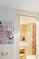 Pop art picture on wall in foyer next to open door with view into bathroom