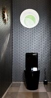Black glossy toilet below round window in wall covered in black and white wallpaper with graphic pattern