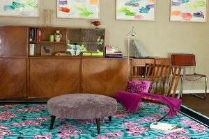 Retro sideboard with glass-fronted top section, framed colourful pictures on wall and patterned turquoise rug in eclectic living area