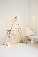Alternative Christmas tree made from folding ladder and take-away cartons used as candle lanterns