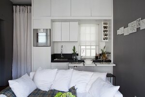 Sofa in front of white kitchen counter with space-saving pull-out tables