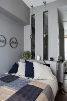 Bed with patchwork cover against grey wall with sill and strip windows