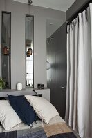 Bed against grey wall with sill and strip windows