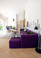 Light-flooded living room with purple sofa and retro standard lamp on herringbone floor