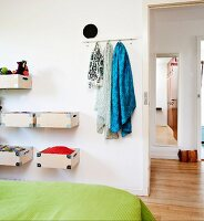 Bed with green bedspread, wooden boxes mounted on wall and scarves hanging from hooks next to open door