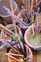 Many paint-stained paintbrushes soaking in pots of water