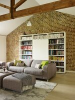 Modern grey sofa and matching ottoman in front of bookcase with cupboard element against brick wall