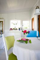 Chair with pale green upholstery at table with white tablecloth and flower arrangements in cottage interior