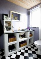 Washstand with masonry base against lilac-painted walls in bathroom with diagonally chequered floor