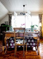 Orchids on antique mahogany desk and chair in rustic living room with white clad, sloping ceiling