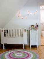 Round, colourful rug in front of cot and white bedside cabinet below sloping ceiling in attic room with string of lighted lanterns