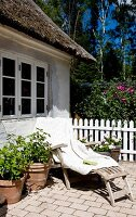 Wooden sun lounger with white blanket and potted plants on terrace outside simple country house in summer atmosphere