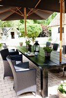 Grey rattan chairs at black table below open parasols on terrace
