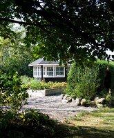 Raised bed with wooden surround on gravel floor in garden; dark, wooden summer house in background