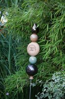 Garden ornament made from baubles on metal rod in front of bamboo bush