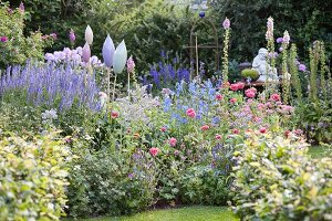 Blue veronica, foxgloves, corydalis and ornaments in flowering garden