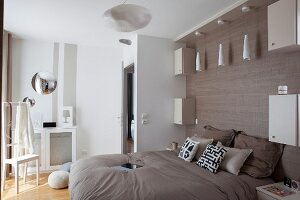 Pendant lamp above double bed against wall with wood-grain effect
