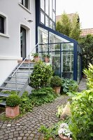 House with metal exterior steps, conservatory and garden path paved in fantail pattern