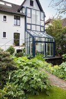 Bushes in various shades of green in front of house with blue steel and glass conservatory structure