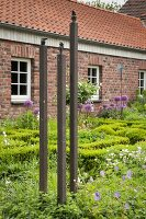 Artwork consisting of 3 columns in front garden of brick farmhouse
