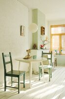 Dining area with round table and green, wooden chairs in bright interior with white wooden floor