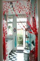 View through draped bead curtain into tiny kitchen with balcony door