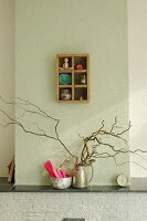 Silver jug of branches and dish of candles on mantelpiece below small, old display case on wall