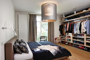 Upholstered bed, modern lamps and open-fronted wardrobe in bedroom
