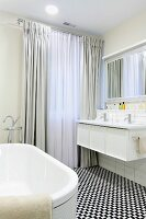 Black and white mosaic floor in elegant bathroom with floor-length curtains