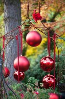 Matte and glossy red baubles hanging from metal trellis arch