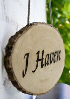 Slice of tree trunk with burnt lettering reading 'I Haven' hanging from cord