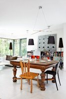 Lamps with black lampshades in open-plan interior with central dining area in eclectic mixture of styles