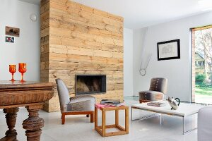 Rustic, untreated wood cladding on chimney breast in eclectic room with retro, upholstered easy chairs and various tables
