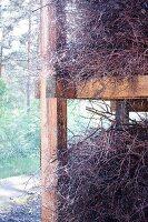 Bundles of brushwood in wooden frame against facade