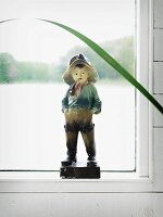 Vintage angler figurine in front of misted window