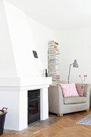 Open fireplace, ecru armchair and stacked magazines on minimalist shelves in corner of living room