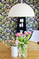 Pink tulips and carnations in vases on wooden table below pendant lamp with white, hemispherical lampshade