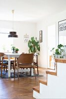 White table and brown chairs below pendant lamps in dining room