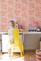 Girl sitting on yellow-painted metal chair at desk against wall with retro floral wallpaper