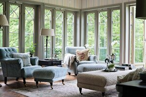 Pale grey armchair and footstool in corner in front of floor-to-ceiling lattice windows
