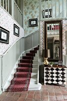 Winding staircase with red runner on white-painted wooden steps in rustic hallway
