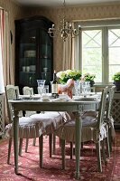 Antique dining table an chairs with ruffled cushions in rustic dining room