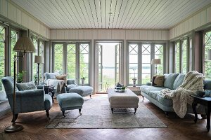 Pale grey armchair, footstool and coffee table in rustic living room with floor-to-ceiling lattice windows