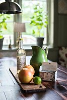 Fruit on wooden board and retro jug on table in front of window