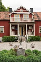 Ornaments and rusty metal candle holders in flowerbed in front of Falu-red country house with porch and balcony