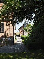 Gravel garden path encircling house with brick façade