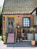Woman in doorway of country house with brick façade holding flowerpot; striped runner on steps