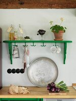 Green-painted wall-mounted shelf with hooks above metal tray leaning against wall on wooden kitchen worksurface